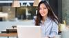 Mujer joven sentada frente a la computadora sonríe y reserva su examen de inglés IELTS online