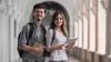 Dos jovenes universitarios revisan fechas para rendir examenes internacionales de ingles IELTS en su tableta