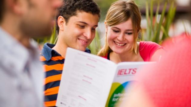 Students looking at an IELTS brochure